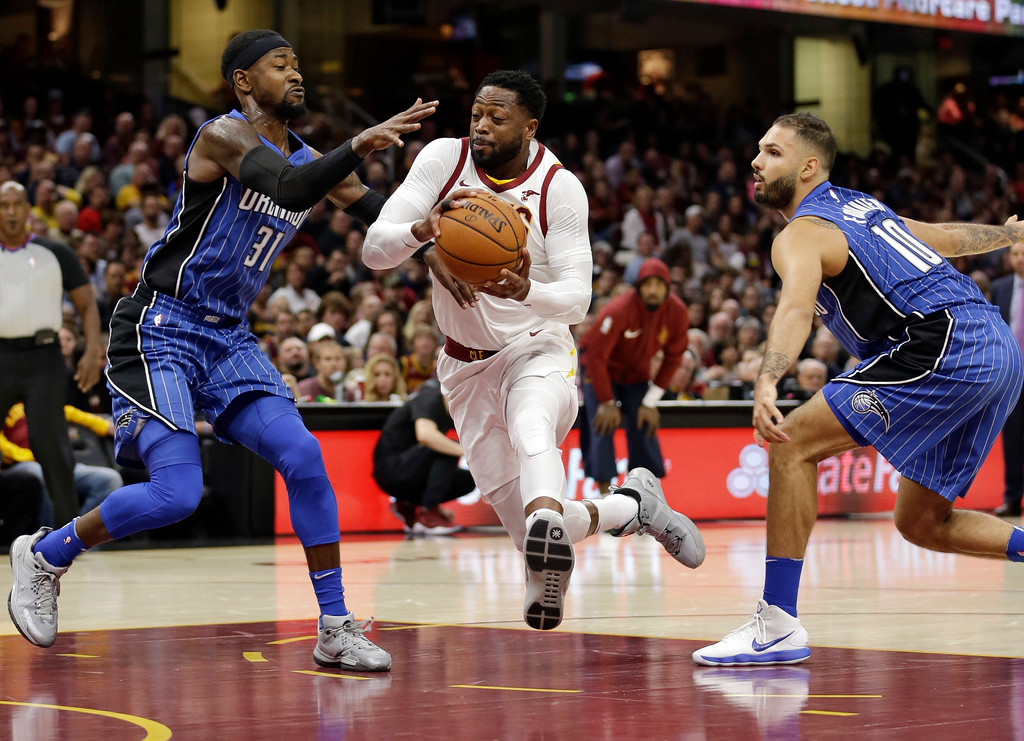 . Cleveland Cavaliers\' Dwyane Wade, center, drives to the basket between Orlando Magic\'s Terrence Ross, left, and Evan Fournier, from France, in the first half of an NBA basketball game, Saturday, Oct. 21, 2017, in Cleveland. (AP Photo/Tony Dejak)