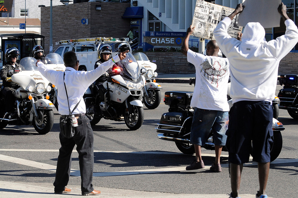 . People protest as LAPD Motor Officers pass by Leimert Park. Crowds gather to protest while a heavy presence of Los Angeles Police Officers patrols the area around Leimert Park at the intersection of, Crenshaw Boulevard and Vernon in Los Angeles, CA. 7/16/2013(John McCoy/LA Daily News)