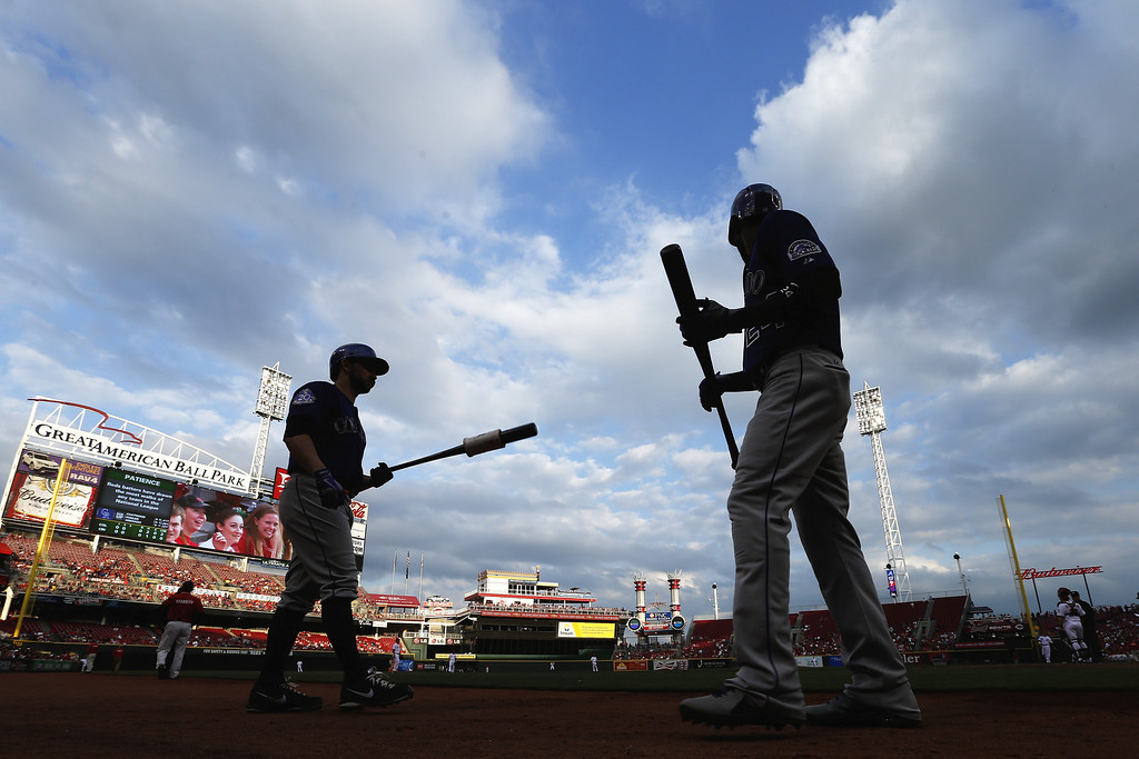 . Dexter Fowler #24 and Tyler Chatwood #32 of the Colorado Rockies prepare to bat against the Cincinnati Reds during the game at Great American Ball Park on June 3, 2013 in Cincinnati, Ohio. (Photo by Joe Robbins/Getty Images)