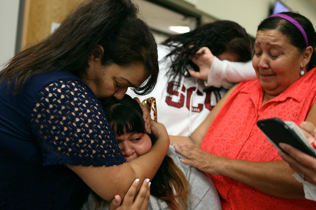 . Family members of Mark Estrada, from left, mother Raquel Estrada, sister Vanesa Estrada, 15, cousin Sofia Lopez, 14, and aunt Carmen Lopez, comfort each other after attending his arraignment hearing at the Hayward Hall of Justice in Hayward, Calif., on Friday, July 24, 2015. Mark Estrada is accused of fatally shooting Hayward Police Sgt. Scott Lunger. (Anda Chu/Bay Area News Group)