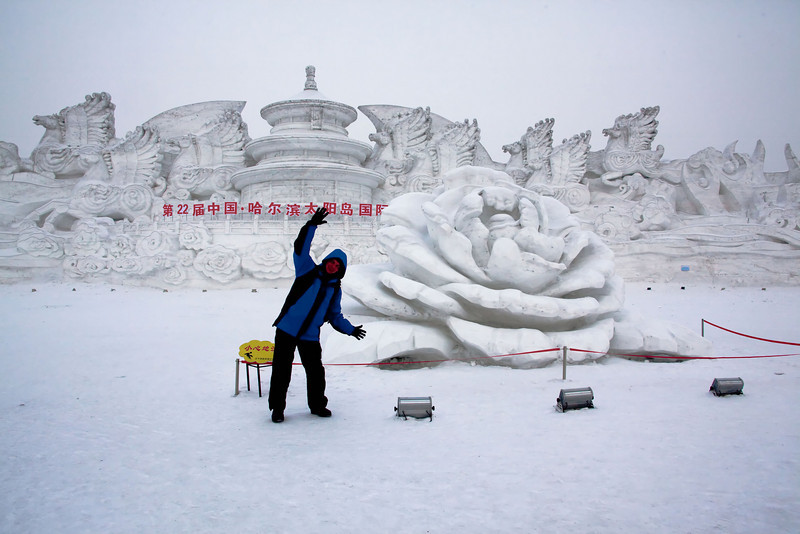 This is a photo of me showing off this beautiful rose sculpted from snow. Notice the winged horses in the background, and the pagoda made out of snow, and all the roses carved into the background as well. Then checkout the next photo which is a photo of my wife next to that background.