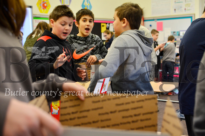 From left, Ian Cieslak, Josh Greenawalt and Preston Green package up boxes to be sent to active duty U.S. troops stationed in the Middle East on Nov. 30, 2018. The boys are sixth graders at Butler Middle School. Tanner Cole/Butler Eagle