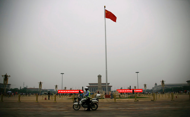 . A policeman stands beside his motorcycle at Tiananmen Square on a hazy day in Beijing June 4, 2013. Tuesday marks the 24th anniversary of a military crackdown on a pro-democracy movement at Beijing\'s Tiananmen Square. REUTERS/Petar Kujundzic