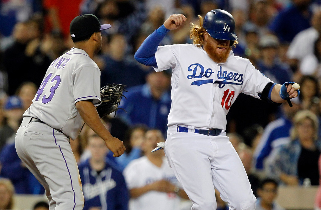 . Los Angeles Dodgersí Justin Turner (10) is out after running out of the base path to avoid the tag by Colorado Rockies third baseman Rafael Ynoa in the fifth inning of a baseball game Saturday, Sept. 27, 2014, in Los Angeles. (AP Photo/Alex Gallardo)