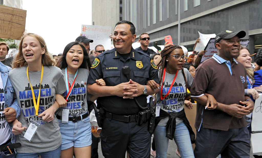 ". Houston Police Chief Art Acevedo, center, and Houston Mayor Sylvester Turner, far right, join demonstrators during a ""March for Our Lives\"" protest for gun legislation and school safety Saturday, March 24, 2018, in Houston. Turner has told several thousand people demonstrating for stricter gun control that adults have a responsibility to stand up and protect all children. (AP Photo/David J. Phillip)"