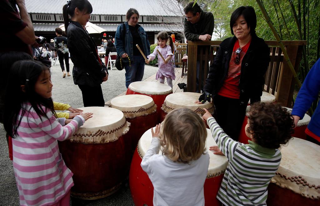 """. Prospective future percussionists check out he Ladies Drumming Group before it takes center stage at Hakone Estate and Gardens during a Lunar New Year of the Snake festival with a \""""Chinese Village Fair\"""" on Sunday afternoon, March 3, 2013 in Saratoga, Calif. (Karl Mondon/Staff)"""