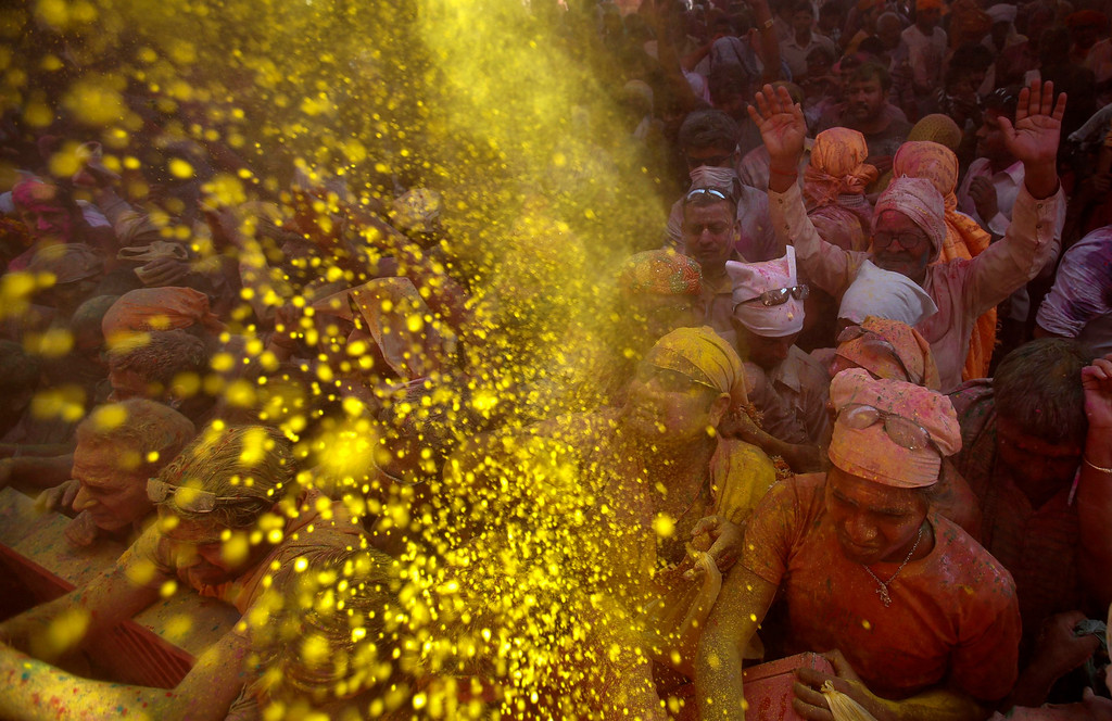 """. Hindu devotees throw coloured powder at a temple during \""""Lathmar Holi\"""" at the village of Barsana in the northern Indian state of Uttar Pradesh March 21, 2013. In a Holi tradition unique to Barsana and Nandgaon villages, men sing provocative songs to gain the attention of women, who then \""""beat\"""" them with bamboo sticks called \""""lathis\"""". Holi, also known as the Festival of Colours, heralds the beginning of spring and is celebrated all over India. REUTERS/Vivek Prakash"""