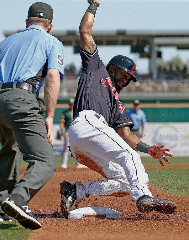 . Cleveland Indians center fielder Austin Jackson, right, slides safely into third base after tagging up at second base as umpire Toby Basner, left, looks on during the first inning of a spring training baseball game against the Oakland Athletics Thursday, March 16, 2017, in Goodyear, Ariz. (AP Photo/Ross D. Franklin)
