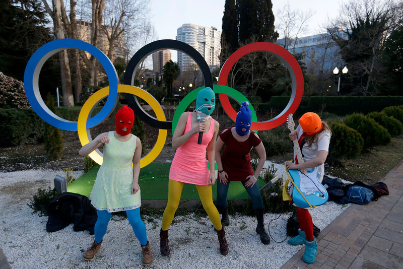 . Members of the punk group Pussy Riot, including Nadezhda Tolokonnikova in the aqua balaclava, center, and Maria Alekhina in the red balaclava, left, perform next to the Olympic rings in Sochi, Russia, on Wednesday, Feb. 19, 2014. Cossack militia attacked the punk group with horsewhips earlier in the day as the artists - who have feuded with Vladmir Putin\'s government for years - tried to perform under a sign advertising the Sochi Olympics. (AP Photo/David Goldman)