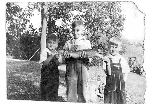 """. ROBERT HOLTZ of Roseville: \""""The photo was taken in the summer of 1941 or 1942, when I was 8 or 9 years old. That is me standing in the middle, with my brother Don holding the tail of the northern and my brother Paul holding the other end. As you can see, Don appears delighted to have been given the privilege of holding the tail.  \""""I caught the northern while fishing for sunfish with my father. His method of dispatching a large fish was to cut off the head. However, once we got home, I decided I wanted my picture taken with my fish. To make that possible, my mother sewed the head back onto the fish.\"""""""