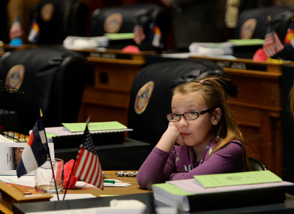 . DENVER, CO. - JANUARY 08: Senator Rachel Zenzinger\'s daughter Olivia, 8, sits at her mothers desk during the first day of the new legislative session at the Colorado Capitol in Denver, CO January 08, 2014. Zenzinger was appointed to fill the seat vacated by former Sen. Evie Hudak. (Photo By Craig F. Walker / The Denver Post)