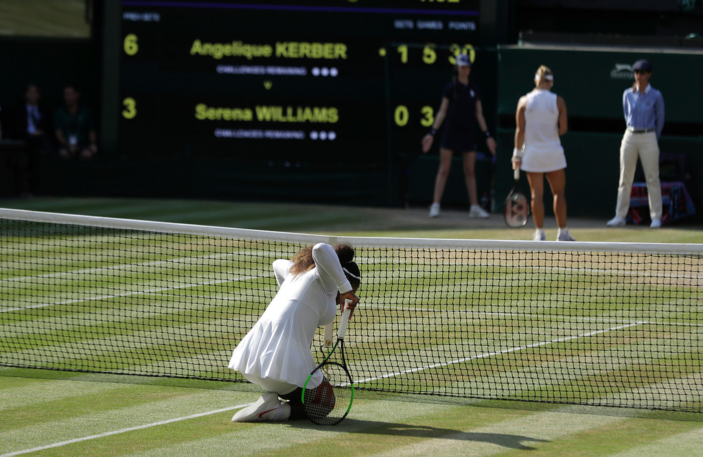 . Serena Williams of the United States kneels by the net after losing a point to Germany\'s Angelique Kerber during their women\'s singles final match at the Wimbledon Tennis Championships, in London, Saturday July 14, 2018.(AP Photo/Ben Curtis)