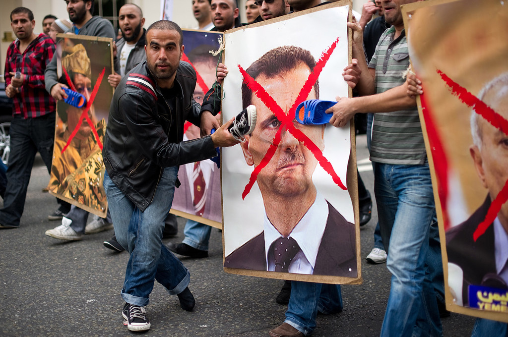 . Protestors hit posters of Syria\'s President Bashar al-Assad (R) and Libyan leader Moamer Kadhafi  with shoes during a demonstration outside the Syrian embassy in London on May 7, 2011.  The demonstration was called to show support for the uprising in Libya, Syria, Bahrain and Yemen. LEON NEAL/AFP/Getty Images
