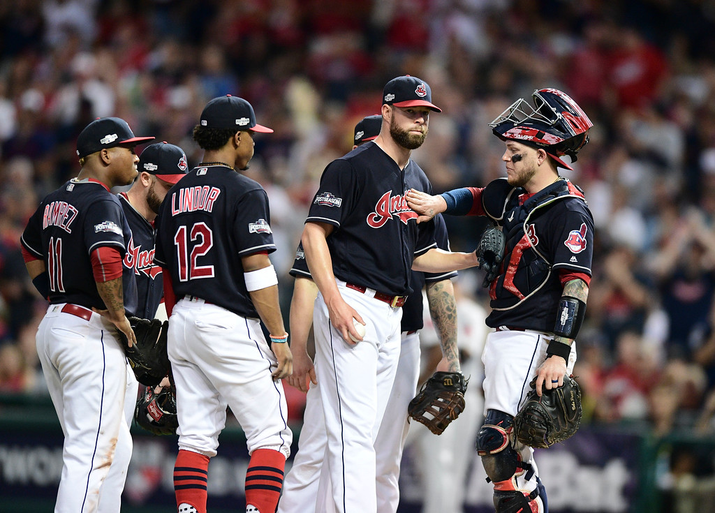 . Cleveland Indians pitcher Corey Kluber, second from right, prepares to leave as catcher Roberto Perez pats him in the eighth inning during Game 2 of baseball\'s American League Division Series against the Boston Red Sox, Friday, Oct. 7, 2016, in Cleveland. (AP Photo/David Dermer)