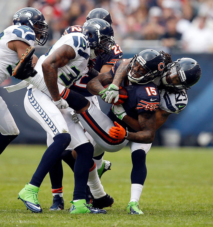 . Chicago Bears wide receiver Brandon Marshall (15) is tackled by Seattle Seahawks cornerback Brandon Browner (L) and free safety Earl Thomas (29) during the first half of their NFL football game at Soldier Field in Chicago December 2, 2012.  REUTERS/Jeff Haynes