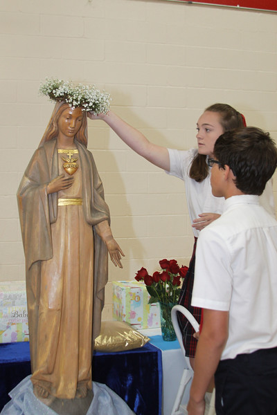 IWA eighth graders Andrea Hoffman and Luis Armstrong crown the statue of Mary during a school Mass in honor of the Mother of God.
