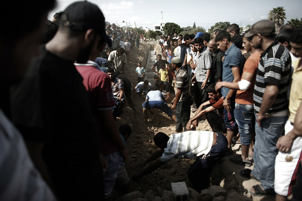 . Relatives and friends bury the bodies of five Palestinians killed, during the funeral in the Central Gaza Strip city of Nusseirat on August 23, 2014. Israeli warplanes pounded Gaza, killing five Palestinians from the same family, two of them children, as the war between Israel and Hamas entered a 47th day. THOMAS COEX/AFP/Getty Images