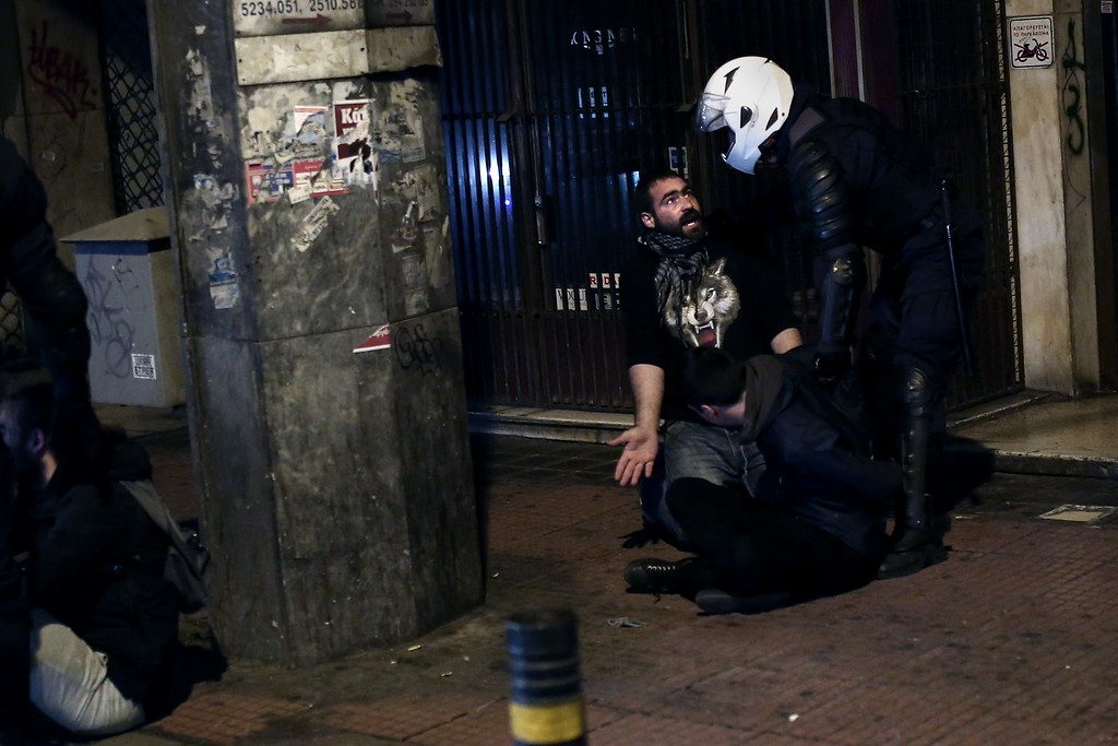 . Riot police arrest a protestor in Athens on December 6, 2014 as youths commemorate the sixth anniversary of the fatal shooting of teenager Alexis Grigoropoulos by a police officer, an event that plunged Greece into weeks of youth riots.  AFP PHOTO / ANGELOS TZORTZINIS/AFP/Getty Images