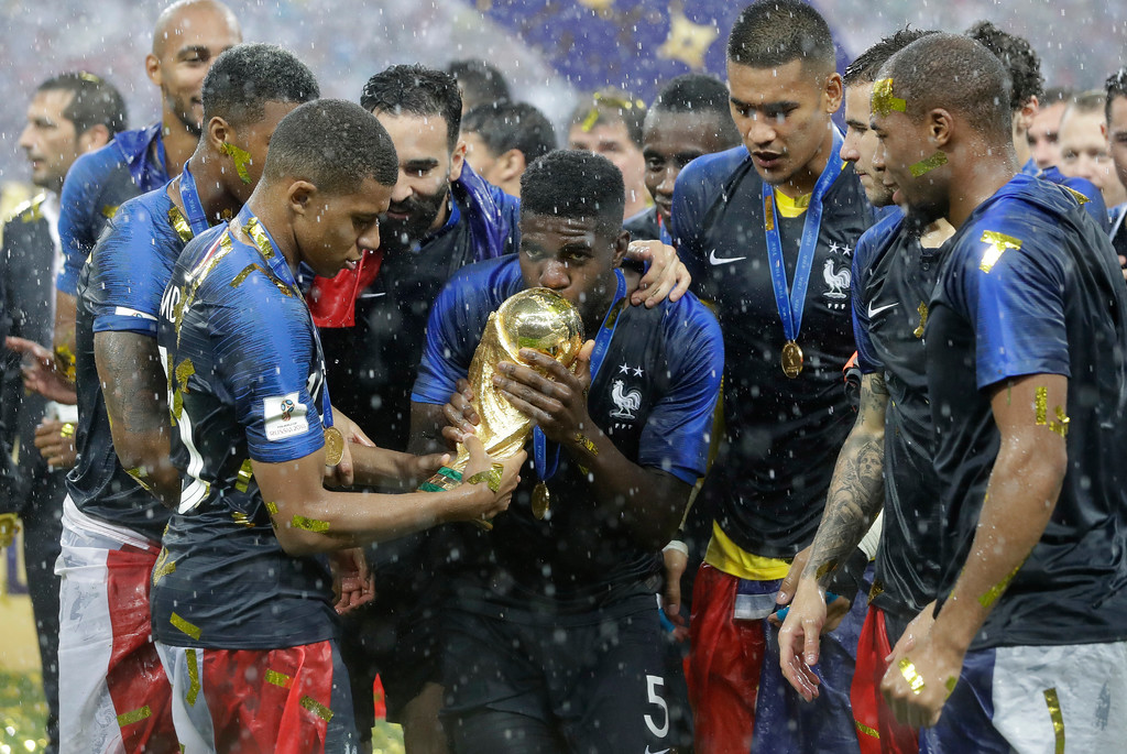 . France\'s Samuel Umtiti, center, kisses the trophy after the final match between France and Croatia at the 2018 soccer World Cup in the Luzhniki Stadium in Moscow, Russia, Sunday, July 15, 2018. France won the final 4-2. (AP Photo/Matthias Schrader)
