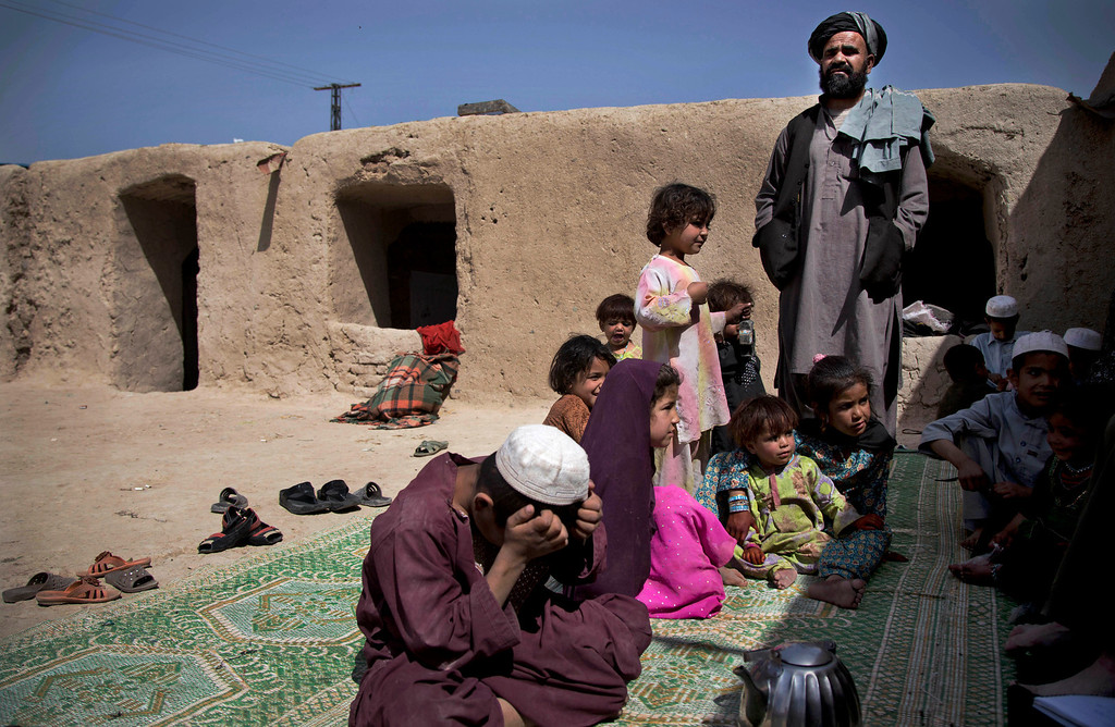 . Maulvi Mohammed Baran, right, the brother-in-law of Masooma, whose husband was killed on March 11, 2012, stands at his home on the outskirts of Kandahar, Afghanistan surrounded by his children and Masooma\'s children. In an interview, Masooma recounted the events of pre-dawn March 11, 2012 when she says a U.S. soldier rampaged through two villages killing 16 people, including her husband. (AP Photo/Anja Niedringhaus)