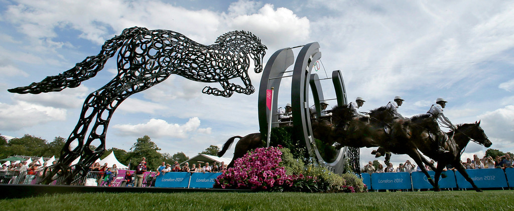 . In this July 30, 2012 file photo and five frame multiple exposure, Andrew Hoy, of Australia, rides Rutherglen as he competes in the equestrian eventing cross-country stage at the 2012 Summer Olympics in London. (AP Photo/Charlie Riedel, File)