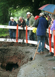Locals and  representatives from the Environmental and Heritage Service watch as measurements are taken of the tunnel.