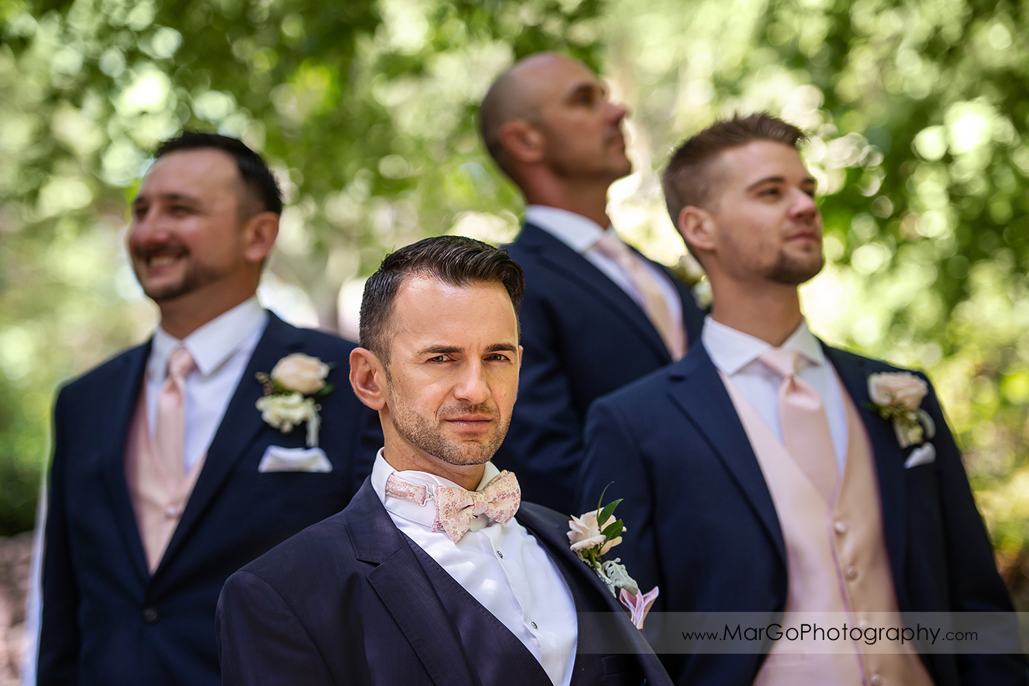 portrait of groom with groomsmen in background in Piedmont Park