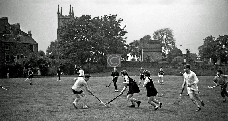 Mixed hockey match on a pitch behind Cathcart Old churchyard. Mini all-weather football pitch attached to a primary school now.   c1965