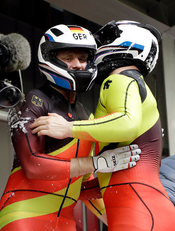 . Driver Nico Walther, right, and Christian Poser of Germany hug after crashing in the finish area in the second run during the two-man bobsled competition at the 2018 Winter Olympics in Pyeongchang, South Korea, Sunday, Feb. 18, 2018. (AP Photo/Michael Sohn)