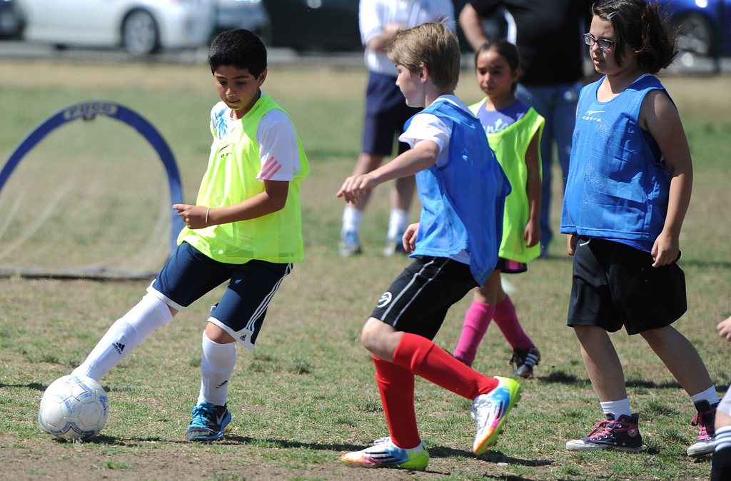 """. Dariush Dahesh kicks the ball past Evan Pritchard. In honor of the AYSO\'s 50th anniversary as the nation�s most active and open youth soccer organization, kids at Balboa Park in Encino will join efforts around the country Saturday--over 500,000 players,125,000 volunteers,100 community-based events and a national soccer festival--to set a world record for the \""""largest pickup game on Earth.\"""" Encino, CA. 5/3/2014(Photo by John McCoy / Los Angeles Daily News)"""