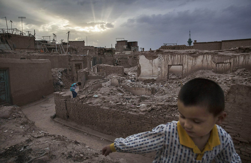 . KASHGAR, CHINA - JULY 29: Uyghur boys walk in the rubble of tradtional houses demolished in recent years to make way for new homes on July 29, 2014 in old Kashgar, Xinjiang Province, China. Nearly 100 people have been killed in unrest in the restive Xinjiang Province in the last week in what authorities say is terrorism but advocacy groups claim is a result of a government crackdown to silence opposition to its policies. China\'s Muslim Uyghur ethnic group faces cultural and religious restrictions by the Chinese government. Beijing says it is investing heavily in the Xinjiang region but Uyghurs are increasingly dissatisfied with the influx of Han Chinese and uneven economic development.  (Photo by Kevin Frayer/Getty Images)