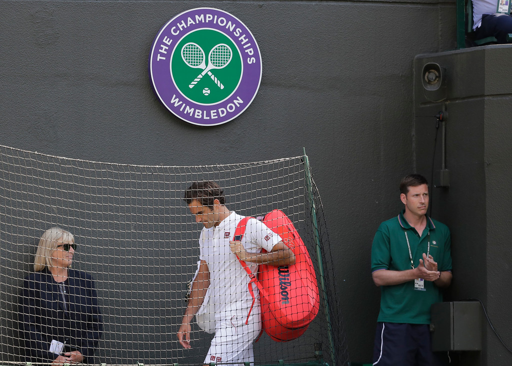 . Switzerland\'s Roger Federer leaves the court after losing his men\'s quarterfinals match against Kevin Anderson of South Africa, at the Wimbledon Tennis Championships, in London, Wednesday July 11, 2018. (AP Photo/Ben Curtis)