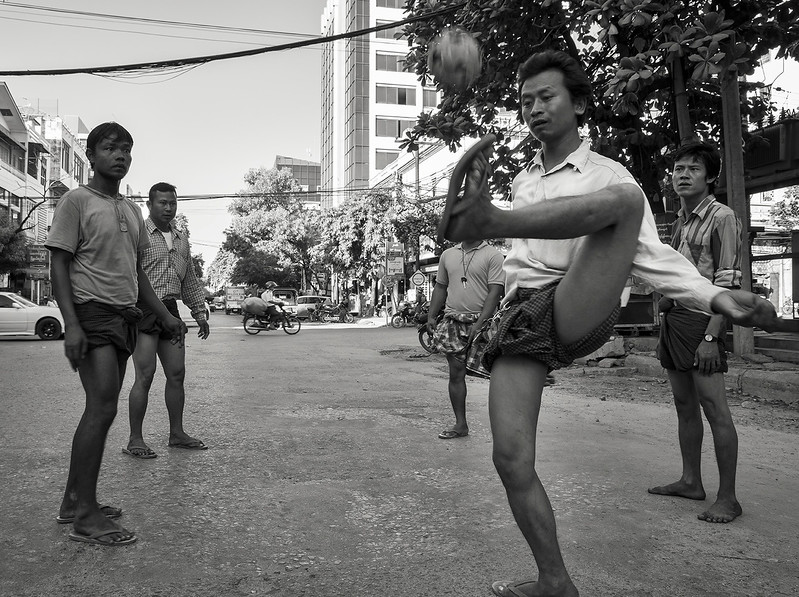 Chinlone, also known as caneball, is the traditional, national sport of Myanmar (Burma). It is non-competitive, with typically six people playing together as one team. The ball used is normally made from handwoven rattan, which sounds like a basket when hit. Similar to the game of hacky-sack, chinlone is played by individuals passing the ball between each other within a circle, without using their hands. However, in chinlone, the players are walking while passing the ball, with one player in the center of the circle. The point of the game is to keep the ball from hitting the ground, all the while passing it back and forth as creatively as possible. The sport of chinlone is played by men, women, and children, often together, interchangeably. Although very fast, chinlone is meant to be entertaining and fluid, as if it were more of a performance or dance.  Myanmar 2017