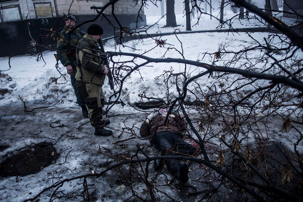 . Separatist rebels look at the body of a man killed near a bus stop that was hit by Ukrainian army shells in Donetsk, eastern Ukraine, Tuesday, Jan. 20, 2015. At least three civilians were killed in shelling Tuesday in eastern Ukraine as fighting continued between government and rebel forces in the separatist-held city of Donetsk.  (AP Photo/Manu Brabo)