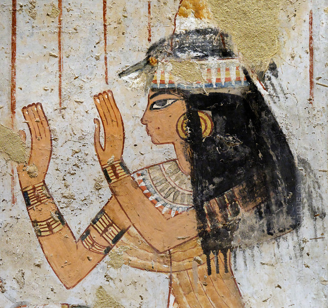 """[EGYPT 29329] 'Worship in Menna's tomb at Luxor.'  Menna's wife Henuttawi has her hands raised in worship in an offering scene on one of the walls of her husband's tomb. She wears an elaborate black wig, held in place by a headband with a lotus flower at the front. The wig is topped with a perfume cone of fragrant grease.  Menna was an 18th dynasty inspector of estates and overseer of harvests and his tomb (TT 69) is located in the Sheikh Abd el Qurnah Necropolis on the Westbank at Luxor. It is one of the socalled """"Tombs of the Nobles"""" and dates to the end of the reign of Thutmosis IV and the beginning of the reign of Amenhotep III. Photo Mick Palarczyk and Paul Smit."""