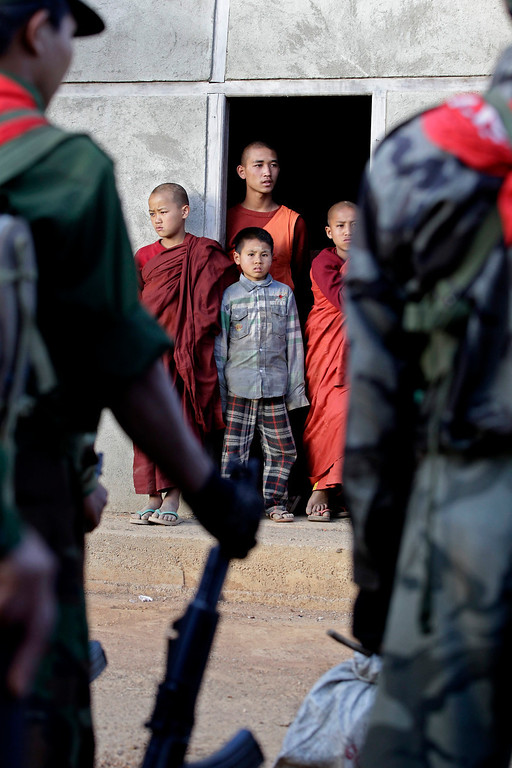 . Buddhist novices and a boy look out from a monestary while  soldiers from Ta-ang National Liberation Army (TNLA), one of the ethnic rebel groups, prepare in Homain village, Nansam Township, Northern Shan State, Myanmar on Jan. 13, 2014. EPA/NYEIN CHAN NAING