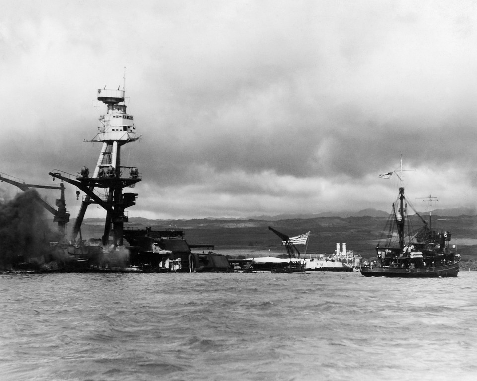 . Battle ship Arizona at pearl Harbor, December 1941. The photo was taken shortley after the battleship was bombed and destroyed during the surprise attack by Japanese forces, December 7, 1941. The vessel at right is a rescue tug. Flag still flying the ship is resting on the bottom of the ocean with decks flooded. (AP Photo)