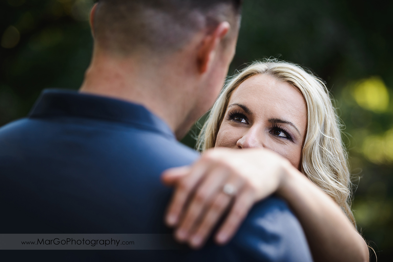 portrait of woman holding hand on arm of man in navy blue shirt during engagement session at San Francisco Golden Gate Park