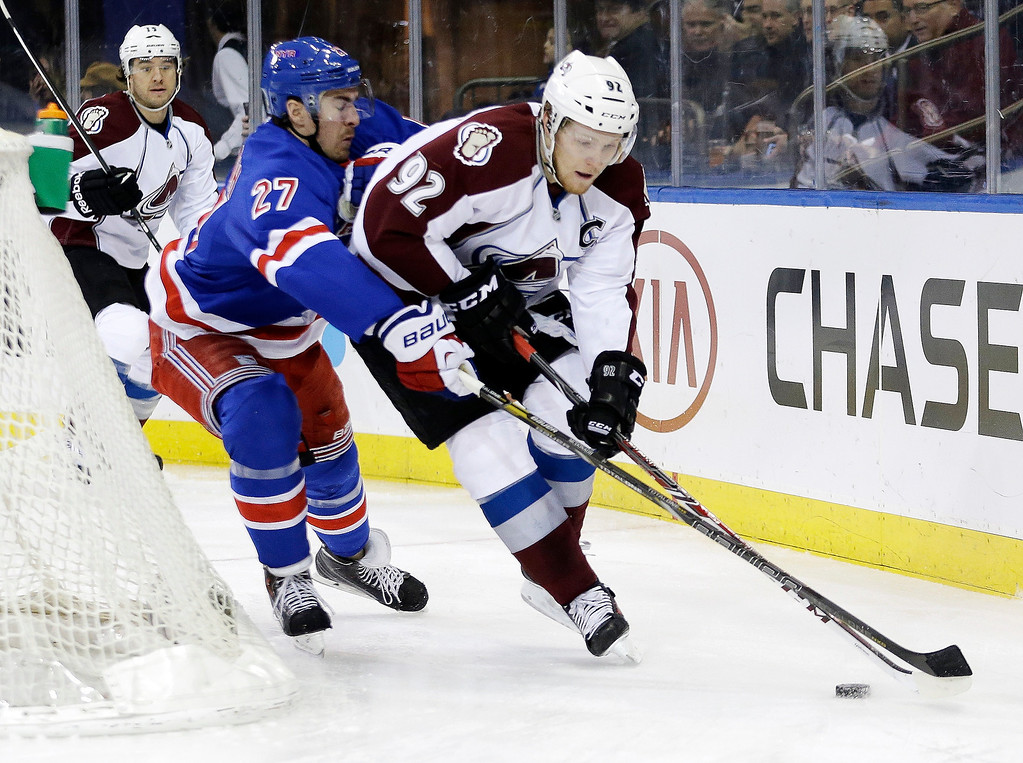 . Colorado Avalanche\'s Gabriel Landeskog (92) and New York Rangers\' Ryan McDonagh (27) fight for control of the puck during the first period of an NHL hockey game, Tuesday, Feb. 4, 2014, in New York. (AP Photo/Frank Franklin II)