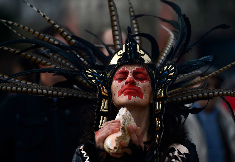Description of . A dancer dressed in a costume and a head-dress performs during a ceremony marking the end of the Mayan age, on December 21, 2012 in Madrid. Ceremonies are being held to celebrate the end of the Mayan cycle known as Bak'tun 13 and the start of the new Maya Era on December 21.  PIERRE-PHILIPPE MARCOU/AFP/Getty Images