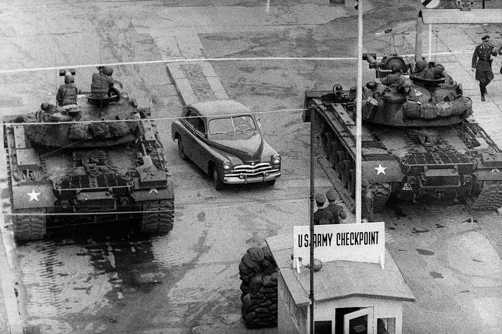 . A car rides between US tanks, in October 1961, across the famous border of the American sector in Berlin, at Checkpoint Charlie crossing point, the only one in the Berlin Wall between East (Soviet sector) and West Berlin (American sector) used only by diplomats and foreigners. The Berlin wall built by the East German government to seal off East Berlin from the part of the city occupied by the three main western powers (USA, Great Britain and France), and to prevent mass illegal emigration to the West. The wall, built along the border between German Democratic Republic (GDR) and Federal Republic of Germany, was the scene of the shooting of many East Germans who tried to escape from GDR. The two countries remained divided until November 1989 when the wall was unexpectedly opened following increased pressure for political reform in GDR.        (Photo /AFP/Getty Images)