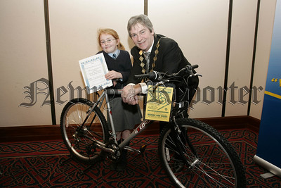 Melissa Caroll from St Peter's Cloughreagh was the winner of a bike at the schools swimming presentations. Also pictured is Newry Lions Club Vice-President Tony Quinn. 07W6N16