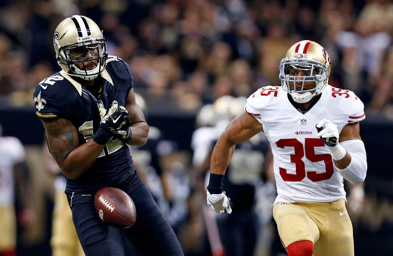 . New Orleans Saints wide receiver Marques Colston (12) drops a pass as San Francisco 49ers free safety Eric Reid (35) pursues in the first half of an NFL football game in New Orleans, Sunday, Nov. 9, 2014. (AP Photo/Jonathan Bachman)
