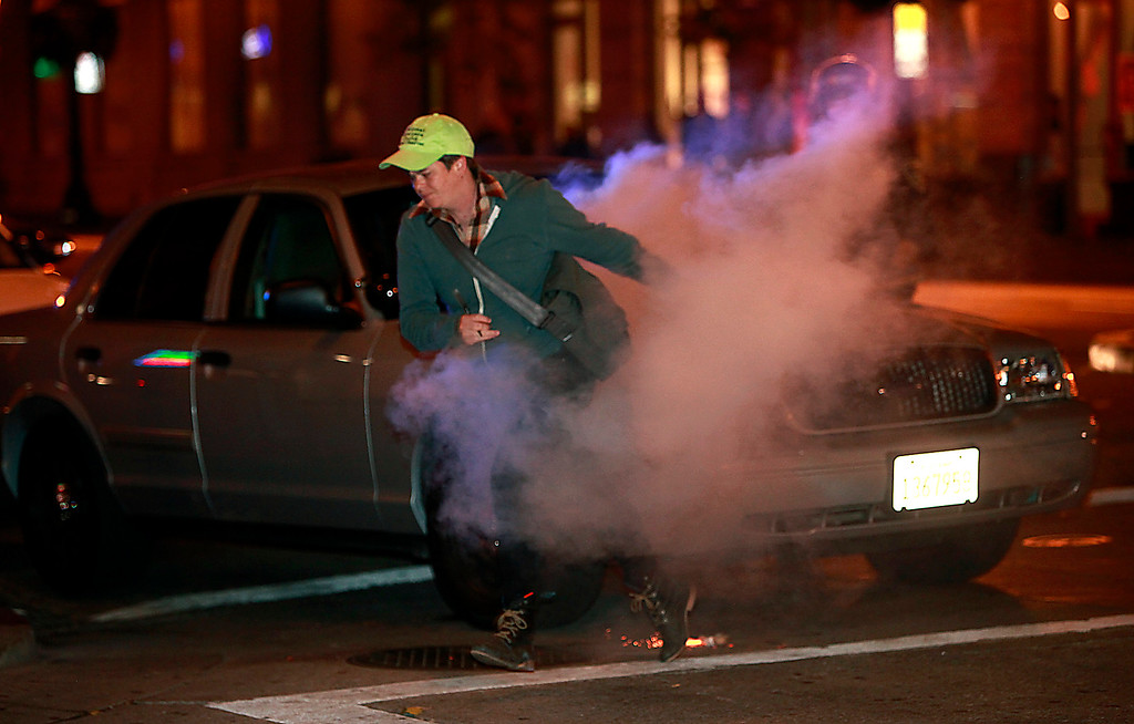 . An observer from the National Lawyers Guild has to scurry away from fireworks tossed at police while she was monitoring arrests on day three of protests over the acquittal of George Zimmerman late Monday evening, July 15, 2013 in Oakland, Calif. (Karl Mondon/Bay Area News Group)