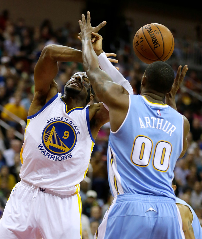 . Golden State Warriors guard Andre Iguodala, left, loses the ball while driving to the basket past Denver Nuggets forward Darrell Arthur during the first half of a preseason NBA basketball game, Thursday, Oct. 16, 2014, in Des Moines, Iowa. (AP Photo/Charlie Neibergall)