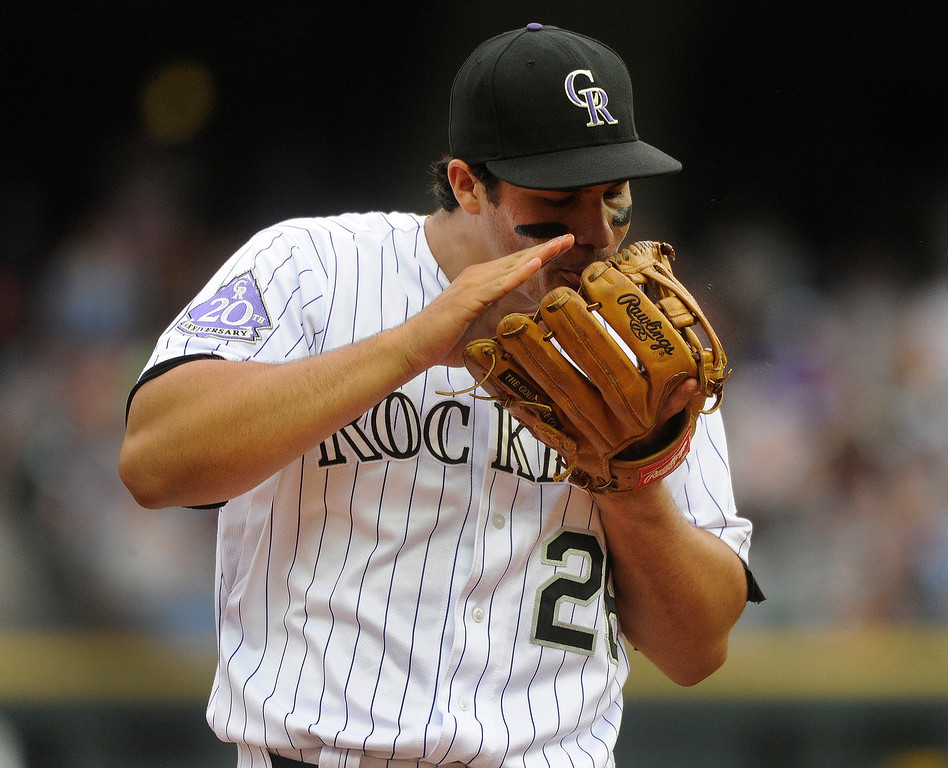 . Rockies infielder Nolan Arendado worked on his glove between innings Thursday. The Colorado Rockies hosted the Miami Marlins at Coors Field Thursday afternoon, July 25, 2013. Photo By Karl Gehring/The Denver Post