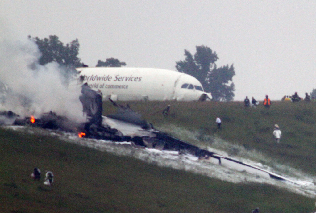 . Debris burns as a UPS cargo plane lies on a hill at Birmingham-Shuttlesworth International Airport after crashing on approach, Wednesday, Aug. 14,  2013, in Birmingham, Ala.  (AP Photo/Hal Yeager)