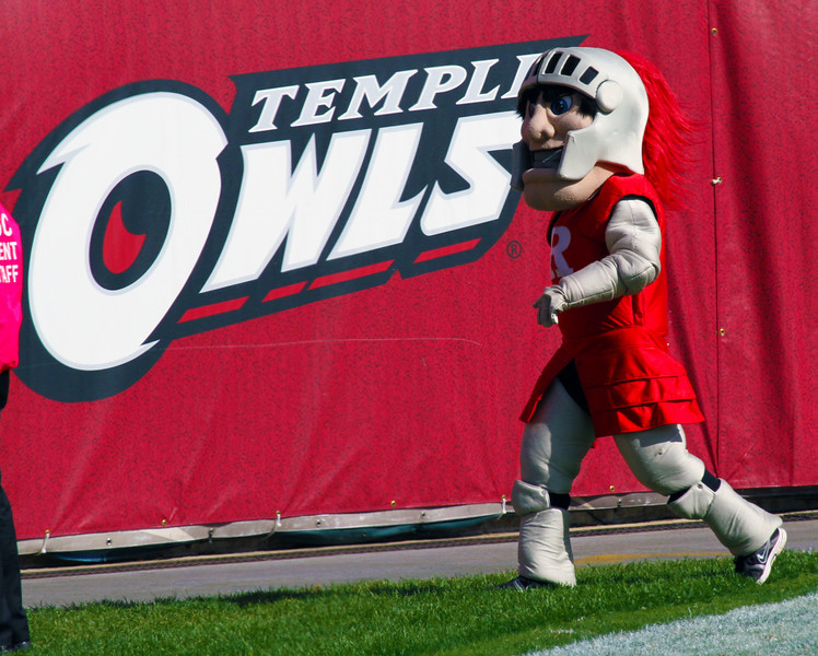 Scarlet Knight mascot passing the Temple Owls banner