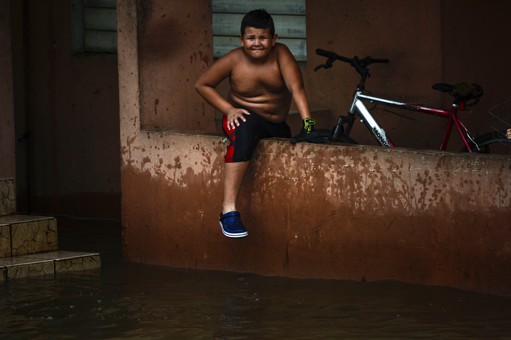 . A boy sits by a flooded area at the Ingenio community after the passing of Hurricane Maria, in Puerto Rico, Friday, September 22, 2017. Because of the heavy rains brought by Maria, thousands of people were evacuated from Toa Baja after the municipal government opened the gates of the Rio La Plata Dam. (AP Photo/Carlos Giusti)