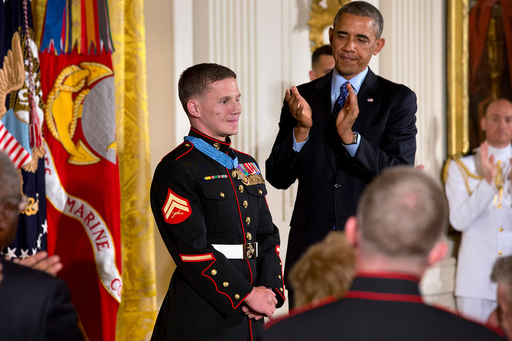 ". President Barack Obama and the crowd applaud retired Marine Cpl. William ""Kyle\"" Carpenter, 24, left, after awarding him the Medal of Honor for conspicuous gallantry, Thursday, June 19, 2014, during a ceremony in the East Room of the White House in Washington.  (AP Photo/Jacquelyn Martin)"